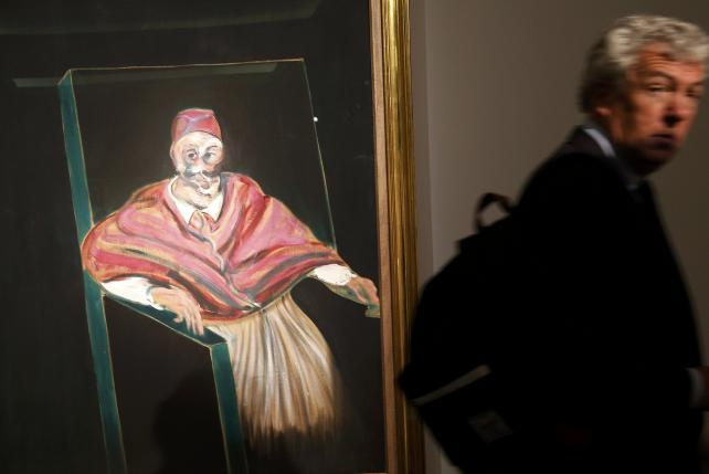 """A visitor passes by """"Study for a Pope I"""" by Francis Bacon at Sotheby's in London"""