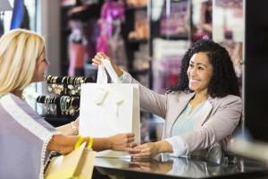 femeie care da unei alte femei o punga de cumparaturi